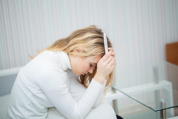 Test de grossesse positif, jeune femme déprimée et triste après avoir examiné le résultat du test de grossesse à la maison