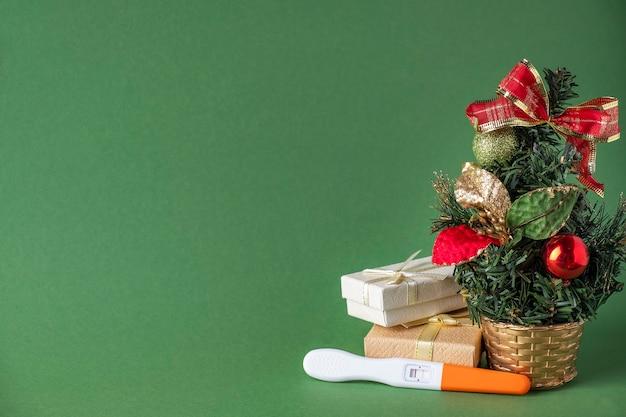 Test de grossesse positif sous l'arbre de noël. cadeau de noël. espace texte