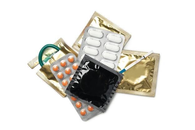 Test de grossesse, préservatifs et pilules isolés sur une surface blanche