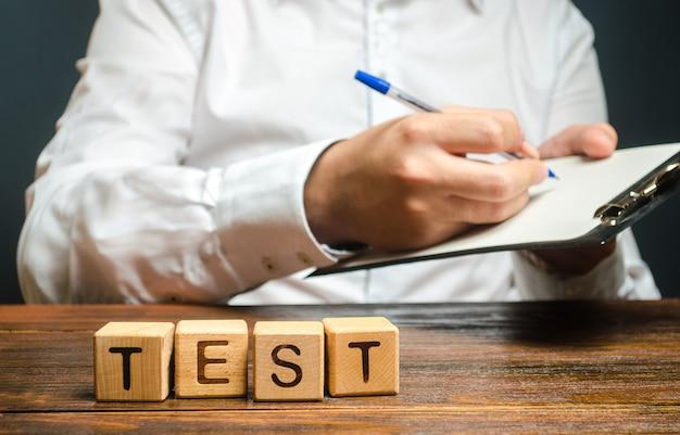 Test de mots et un homme avec un presse-papiers en arrière-plan audit de contrôle qualité