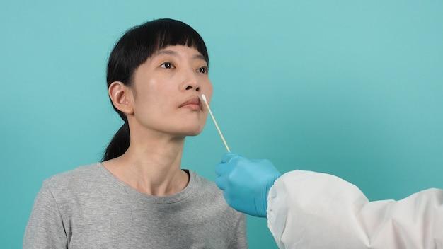 Test pcr rt. femme avec test d'écouvillonnage covid 19. test de coronavirus pendant l'épidémie. medic prélevant un échantillon pour le test de virus. fond vert bleu. docteur en test d'écouvillonnage de costume d'epi. test d'antigène rapide de virus.