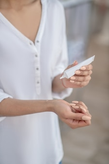 Test, produit d'entretien. gros plan des mains féminines et produit cosmétique au poignet et dans le tube, visage non visible