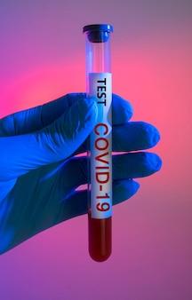 Test sanguin avec infection à coronavirus dans un tube à essai médical dans la main d'un médecin sur fond rouge