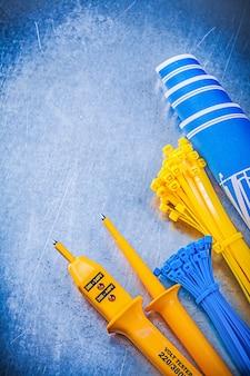 Testeur électrique jaune serre-câbles autobloquants plans de construction bleus sur table métallique, concept d'électricité