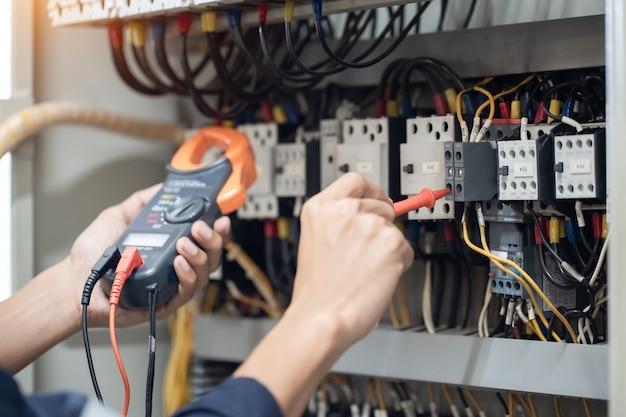 Testeur de travail d'ingénieur électricien mesurant la tension et le courant de la ligne électrique dans le contrôle de l'armoire électrique, contrôle de concept le fonctionnement du système électrique.