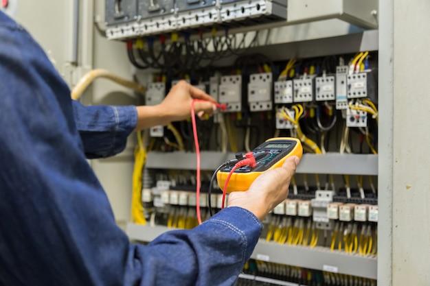Testeur de travaux d'ingénieur électricien mesurant la tension et le courant de la ligne électrique de puissance dans le contrôle d'armoire électrique.