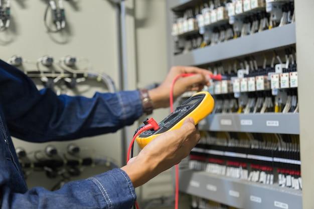 Testeur de travaux d'ingénieur électricien mesurant la tension et le courant de la ligne électrique de puissance dans le contrôle d'armoire électrique