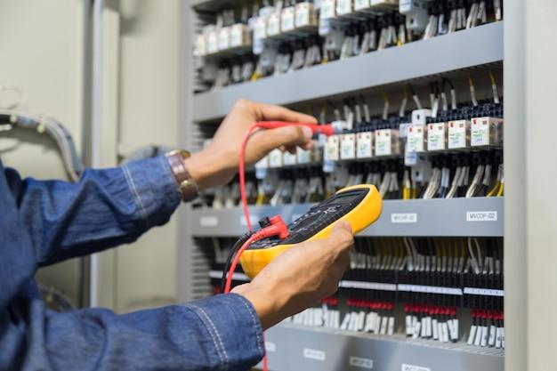 Testeur de travaux d'ingénieur électricien mesurant la tension.