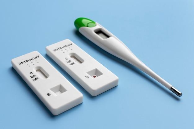 Tests covid avec thermomètre sur fond bleu