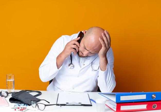 Avec la tête abaissée jeune médecin de sexe masculin chauve portant une robe médicale et un stéthoscope assis au bureau avec des outils médicaux parle au téléphone sur orange