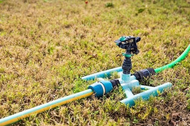 Tête d'arrosage pour pulvériser de l'eau sur l'herbe verte.