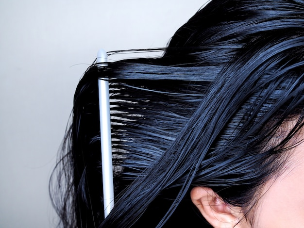 Tête d'asiatique aux longs cheveux noirs, se peignant avec une brosse à cheveux. santé de la racine des cheveux.