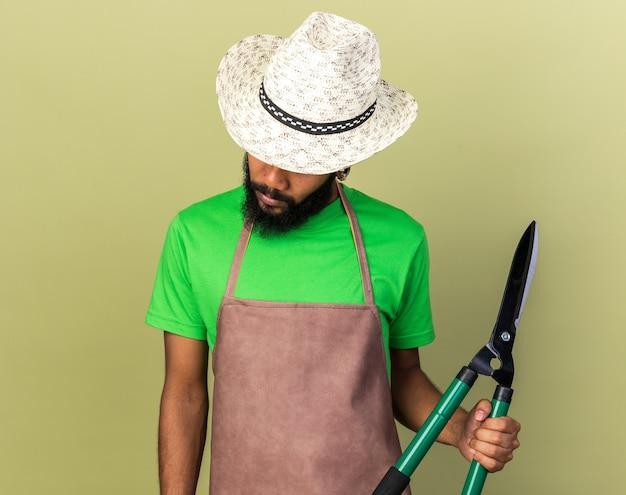Avec la tête baissée jeune jardinier afro-américain portant un chapeau de jardinage tenant des tondeuses isolées sur un mur vert olive