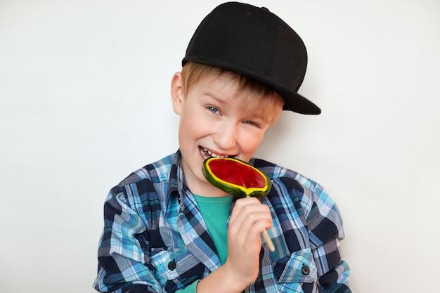 Tête de beau petit garçon tenant et sucer la sucette avec une expression joyeuse et joyeuse