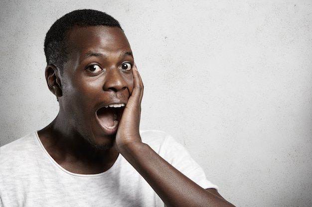 Tête d'un bel étudiant africain excité et totalement choqué regardant en pleine incrédulité, couvrant sa bouche ouverte avec la main, surpris par des nouvelles inattendues et positives.