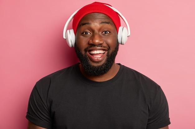 Tête de bel homme avec un sourire à pleines dents, a les dents blanches, délivre le son aux oreilles via un casque, écoute de la musique dans un casque sans fil