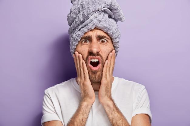 La tête d'un bel homme touche les joues, a une expression de visage insatisfaite, se rend compte qu'il a la peau problématique, garde les mains sur les joues, porte un t-shirt blanc décontracté, une serviette enveloppée sur la tête, se tient à l'intérieur