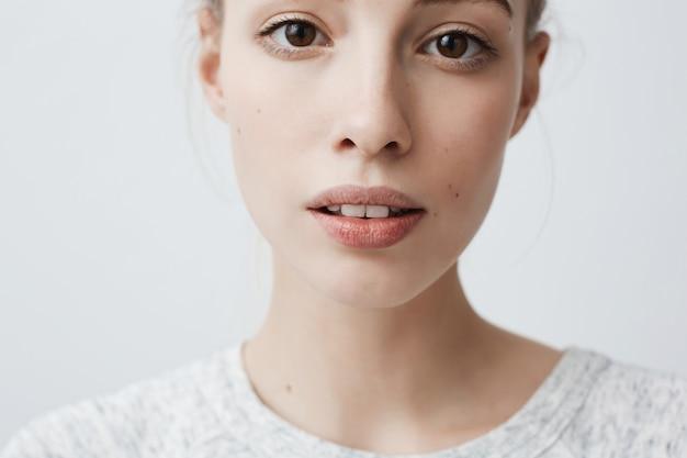 Tête de belle charmante jeune femme regardant avec les lèvres légèrement entrouvertes