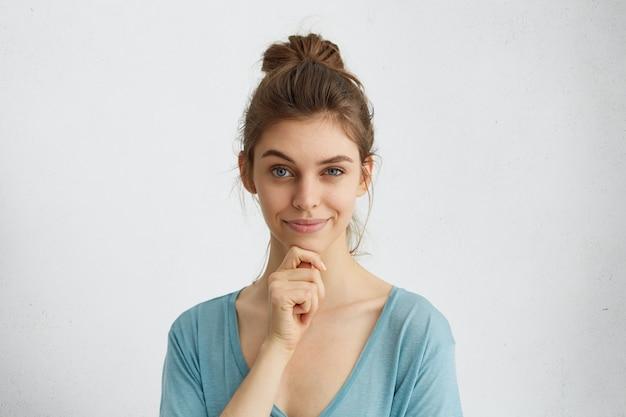Tête de belle femme ayant l'air rusé levant son sourcil et tenant la main sur le menton ayant des plans délicats dans son esprit.