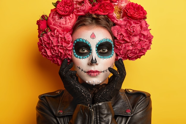 Tête de belle femme sérieuse avec le maquillage du crâne, le visage peint par l'artiste, porte des vêtements noirs, veut avoir l'air effrayant, pose sur fond jaune. vacances mexicaines traditionnelles