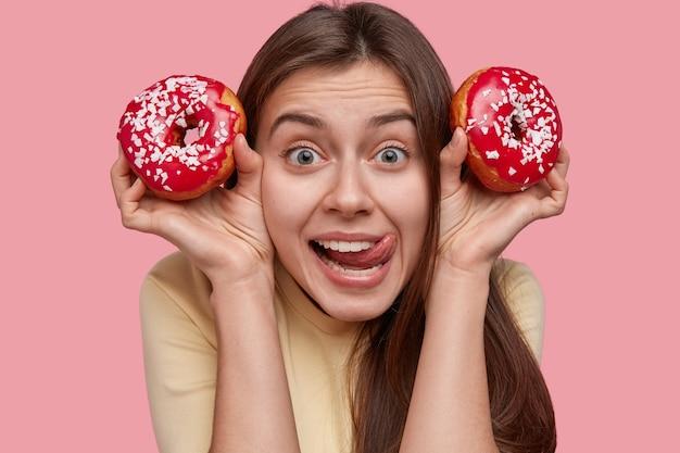 Tête de belle jeune femme lèche les lèvres, regarde avec une expression joyeuse, porte deux délicieux beignets, a les cheveux noirs, apprécie une collation