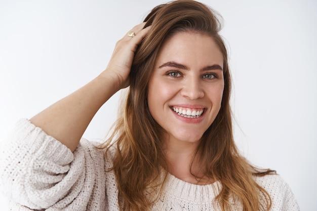 Tête charismatique charmante femme européenne courir la main dans les cheveux vérifier la coupe de cheveux sourire idiot mignon flirter souriant dents blanches parler avec désinvolture rire sentiment heureux fond blanc