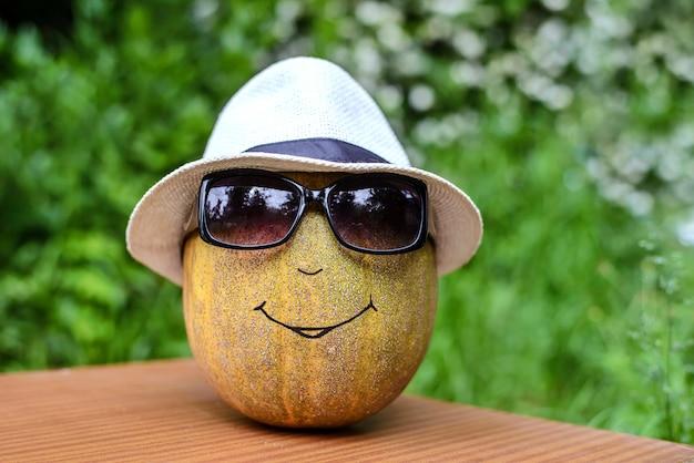 Tête de citrouille avec un chapeau et des lunettes de soleil
