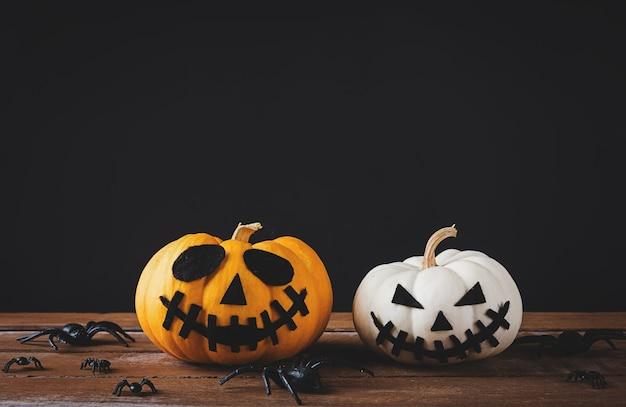 Tête de citrouilles fantôme jack lantern sourire effrayant et araignée sur table en bois