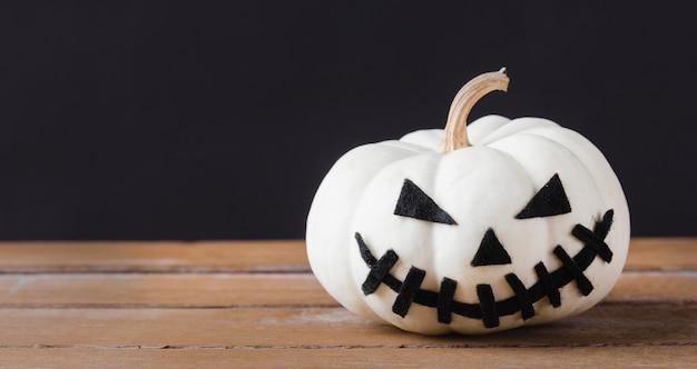 Tête de citrouilles fantôme jack lantern sourire effrayant sur table en bois