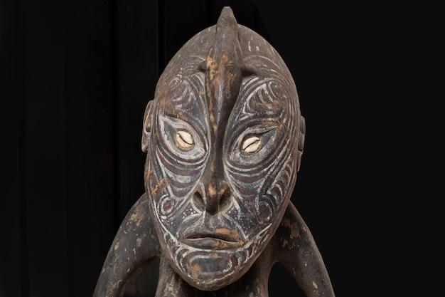Tête, détail d'une statue de femme en bois peint sur fond noir. fermer