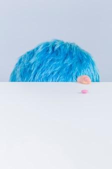 Tête et le doigt de cheveux bleus au bord de la table avec la pilule rose