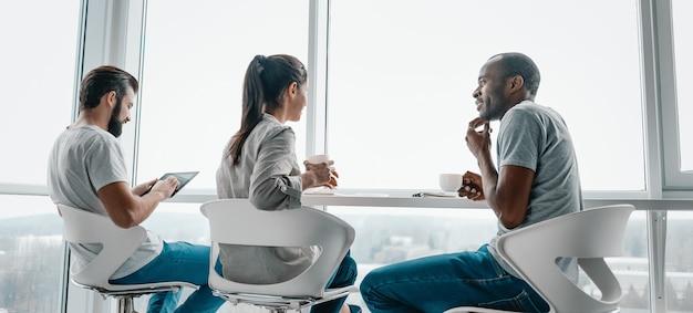 L'en-tête du site web de collègues multiculturels plaisante pendant la pause-café sur le lieu de travail