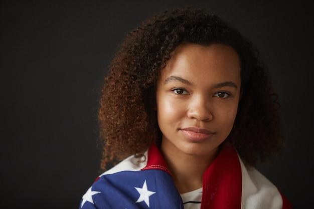 Tête et épaules portrait de jeune fille afro-américaine enveloppée dans le drapeau américain