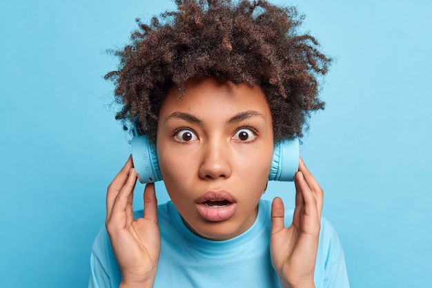 Tête d'une femme aux cheveux bouclés stupéfaite et impressionnée qui a les yeux sortis qui garde son souffle écoute de la musique dans des écouteurs sans fil choqué d'entendre un son très fort isolé de manière inattendue sur le mur bleu