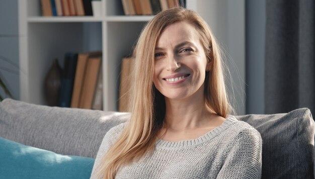 Tête de femme blonde mature avec un sourire rayonnant assis sur un canapé dans un appartement en regardant la caméra