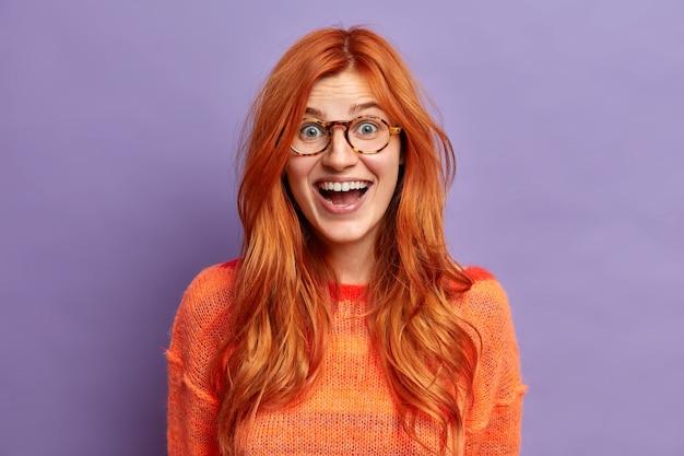 Tête de femme européenne au gingembre excitée regarde avec une expression de visage heureux ne peut pas croire que son succès porte des lunettes et un pull.