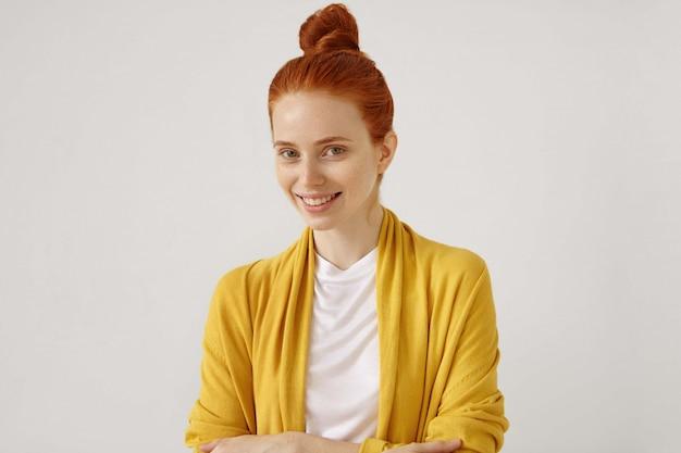 Tête de femme heureuse au gingembre d'apparence européenne avec des taches de rousseur et des yeux verts portant un cardigan jaune à la recherche et souriant, debout isolé