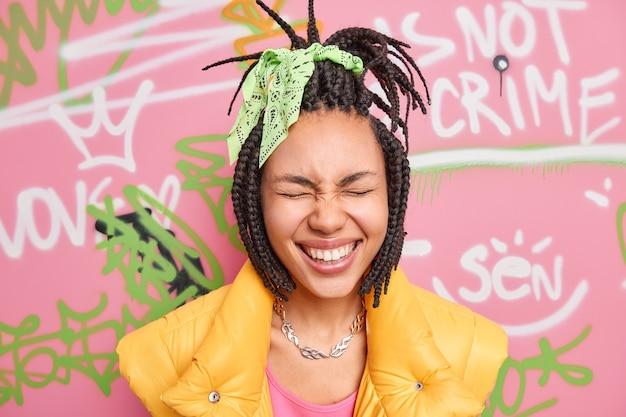 Tête de femme ravie ferme les yeux sourit à pleines dents s'amuse en milieu urbain porte des vêtements élégants pose contre le mur de graffitis de rue exprime des émotions positives