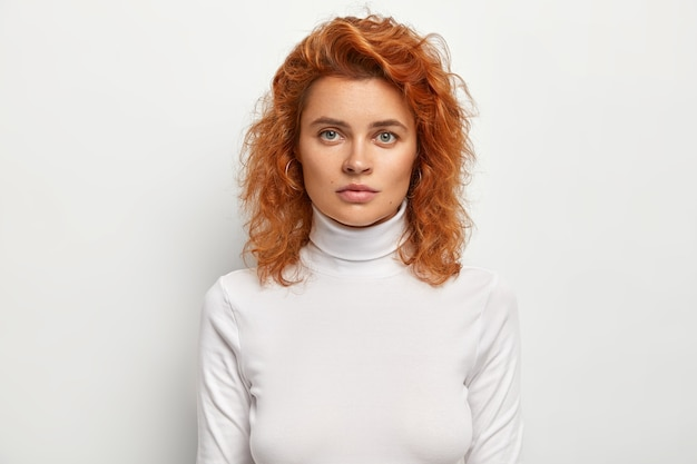 Tête de femme sérieusement belle regarde sérieusement, a une expression de visage confiante, a les cheveux ondulés roux, porte un col polo décontracté, isolé sur un mur blanc. concept de personnes et de beauté