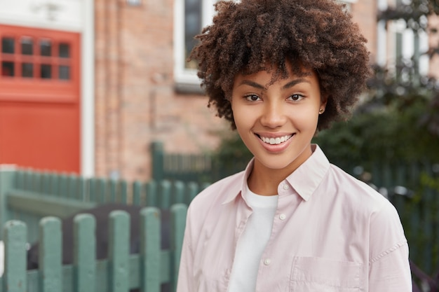 Tête de femme souriante à la peau sombre avec des dents parfaites, se repose en plein air, profite d'une atmosphère calme rurale, regarde directement, habillée avec désinvolture. gens