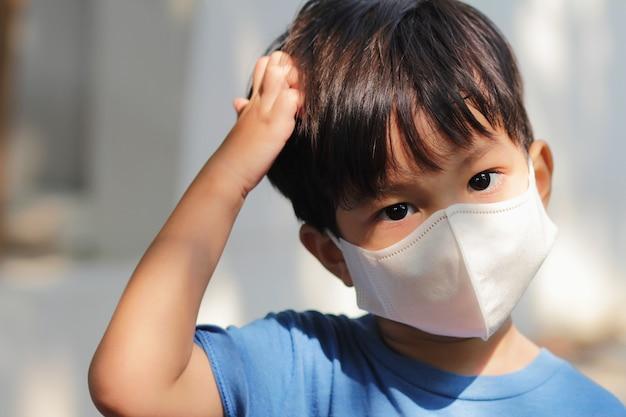 Tête fermée d'un enfant portant un masque. petit garçon asiatique dans l'épidémie de virus corona et le concept de crise pm 2.5.