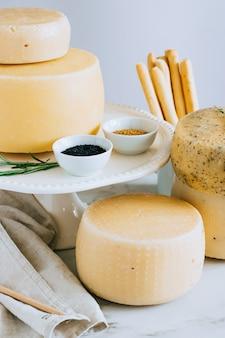 Tête de fromage cachotta assortie avec cumin noir, fenugrec et fines herbes dans un présentoir à gâteaux