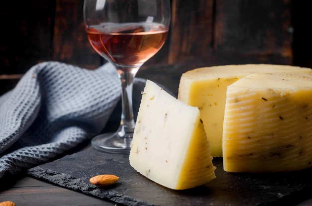 Tête de fromage fait maison à la lavande sur une vieille planche de bois sombre et un verre de vin sur la table. produits laitiers frais, aliments biologiques sains. délicieux apéritif.