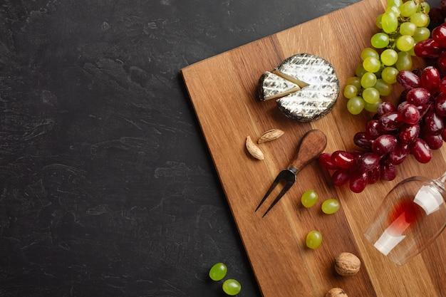 Tête de fromage, grappe de raisin, miel, noix et verre à vin sur planche de bois et fond noir
