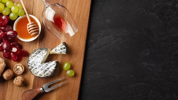 Tête de fromage, grappe de raisin, miel, noix et verre à vin sur planche de bois