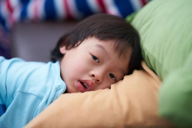 Tête de garçon endormi s'allonger sur un oreiller moelleux avec regard