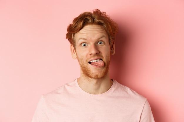 Tête de gars rousse drôle montrant la langue, faisant des grimaces stupides à la caméra, debout joyeux sur fond rose.