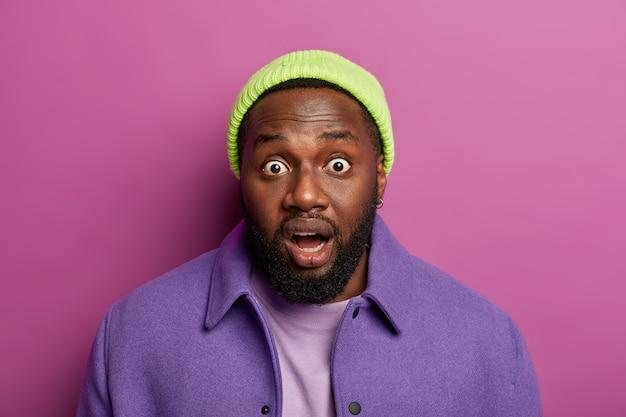 La tête d'un homme barbu noir surpris regarde avec des yeux écarquillés, reste sans voix, porte un chapeau et une veste violette, se sent ravi et étonné