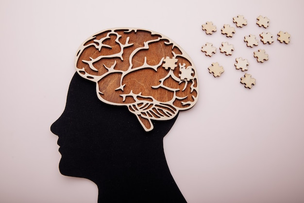 Tête d'homme avec cerveau et puzzle en bois. maladie d'alzheimer, démence et concept de santé mentale.