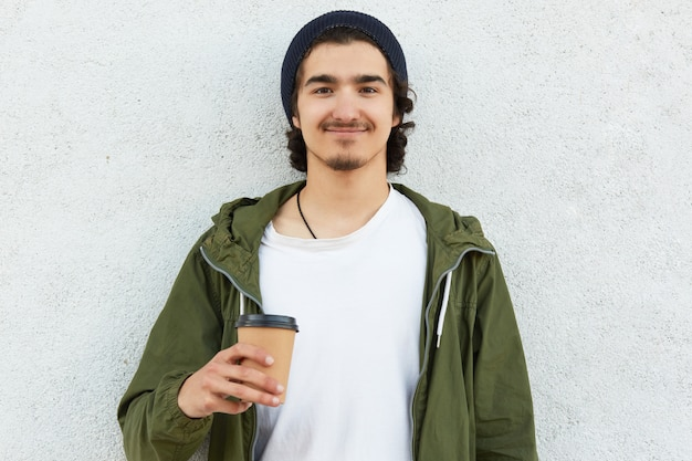 Tête d'homme hipster heureux avec du café à emporter, vêtu d'un t-shirt blanc et d'une veste verte, aime le temps libre, porte un chapeau noir, des mannequins sur fond blanc, a les cheveux bouclés. les gens et boire